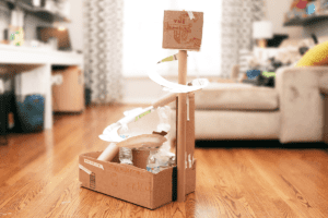 Handmade marble run made out of cardboard, paper plates, and water bottles.